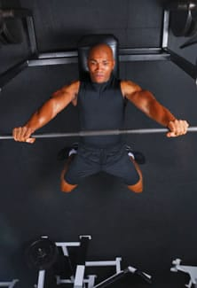 Man Lifting Weights on Bench Press Burning Calories During Workout